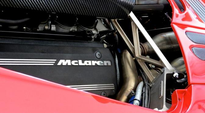 A bright red McLaren F1 in the paddock at Laguna Seca